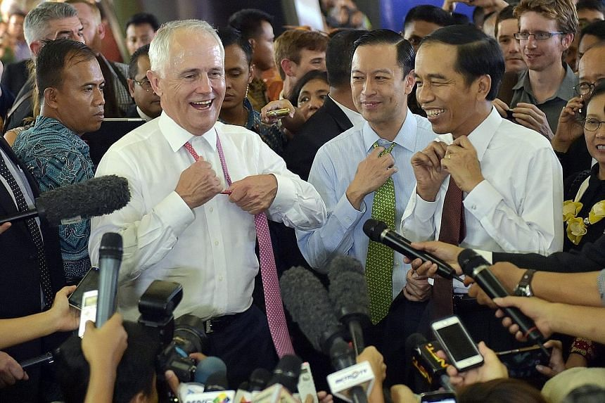 Australian Prime Minister Malcolm Turnbull and Indonesian President Joko Widodo shedding their neckties during a walkabout at Jakarta's Tanah Abang market yesterday. Mr Turnbull is said to be the first foreign head of state invited by Mr Joko to go o