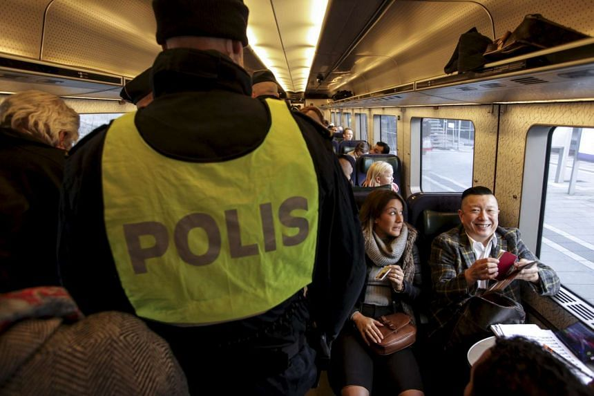 Police officers conduct identity checks on train passengers at the Denmark-Sweden border.