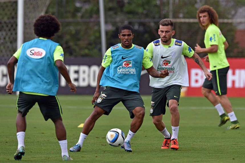 Brazil's player Douglas Costa (second from left) vies for the ball with Lucas Lima (second from right) during a training session in Sao Paulo, Brazil, on Nov 9, 2015.