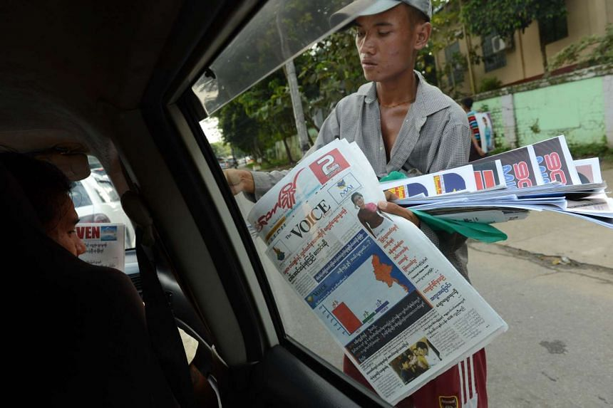A vendor selling newspapers showing election results for Aung San Suu Kyi's NLD party in Yangon on Nov 12, 2015.