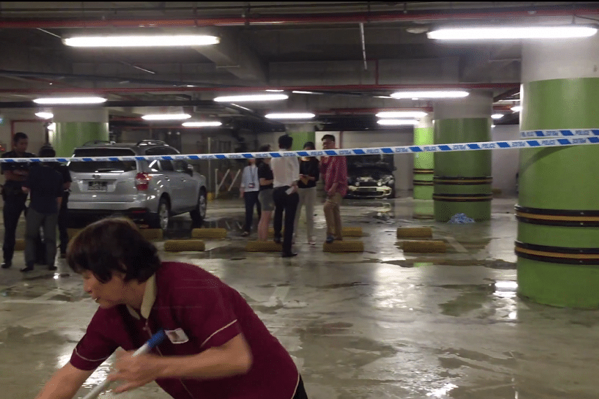 Cleaners are seen sweeping away the water in the Tampines One carpark after the fire was put out.