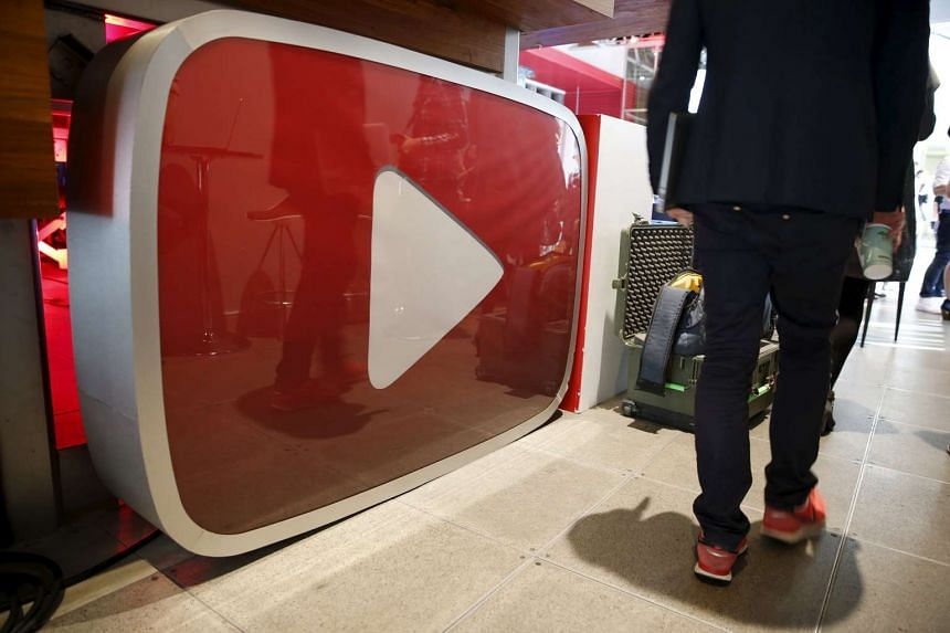 A man walking past a YouTube logo at the YouTube Space LA in Los Angeles, California.