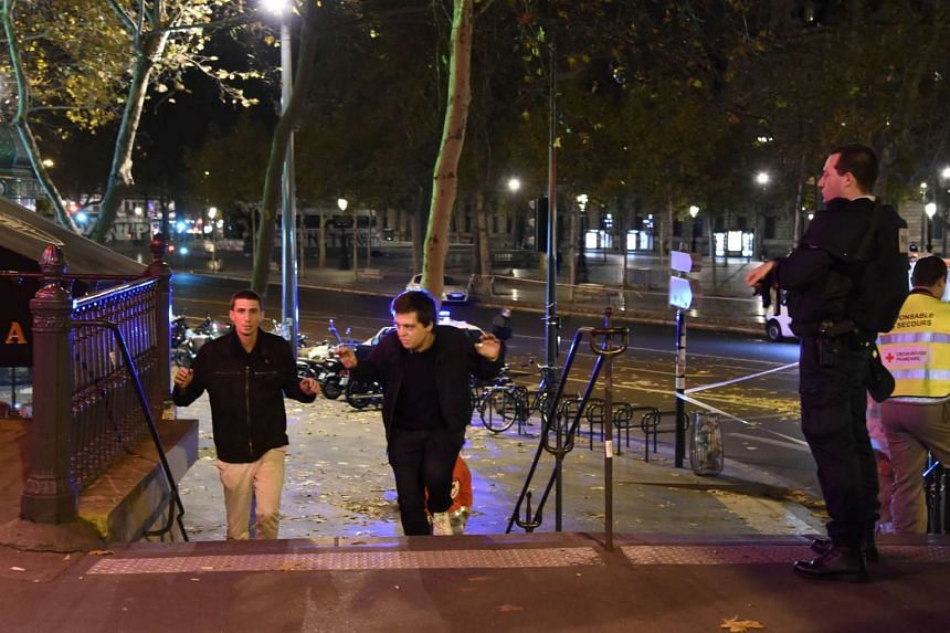 Two men evacuating the Place de la Republique square in Paris as a police officer looks on, after several shootings on Nov 13, 2015.