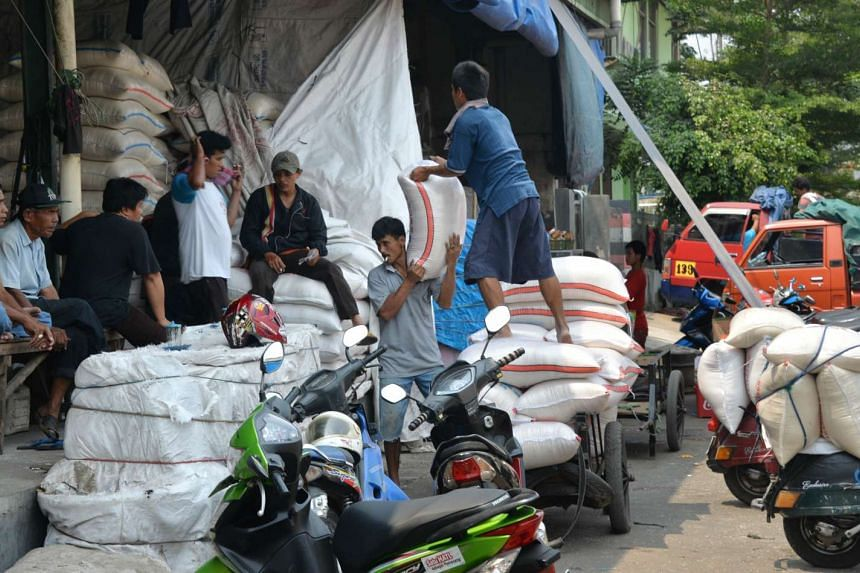 Workers unloading sacks of rice from farmers at the biggest rice market in Jakarta on Sept 9, 2015.