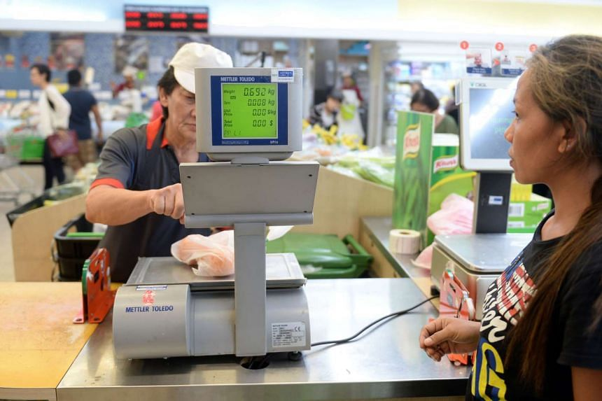 A retail assistant handling the weighing scales at an NTUC FairPrice outlet at Toa Payoh Hub.