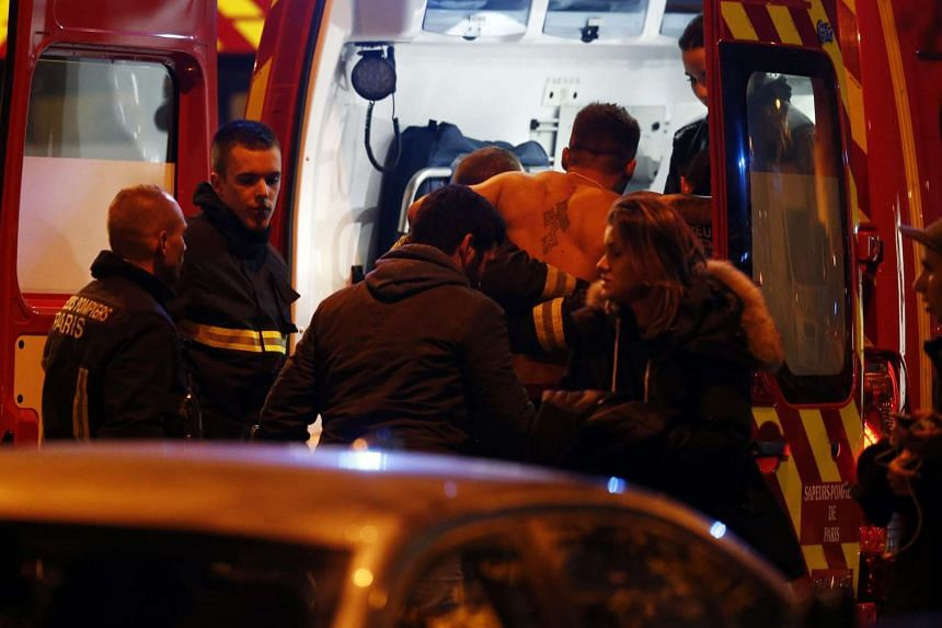 A wounded man being helped into a fireman truck next to the Stade de France where three bombs exploded on late Nov 13, 2015.