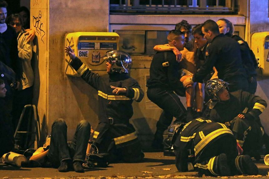 French firemen aiding an injured individual near the Bataclan concert hall following fatal shootings in Paris, France on Nov 13, 2015