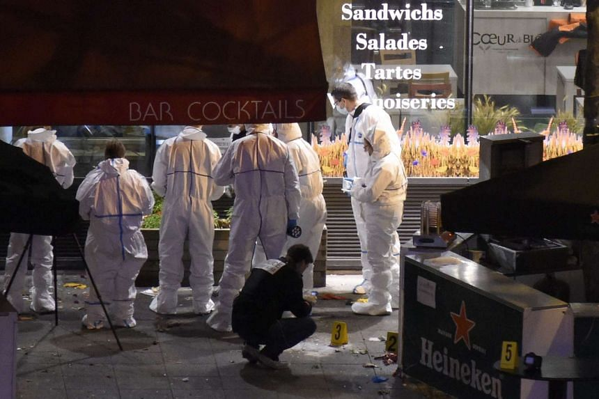 Forensic experts inspecting the site of an attack at a restaurant outside the Stade de France stadium in Saint-Denis, north of Paris, late on Nov 13, 2015.