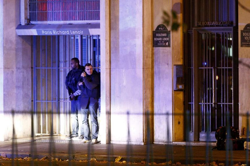 French police officers taking cover outside the scene of a hostage situation at the Bataclan theatre in Paris, France, Nov 13, 2015.