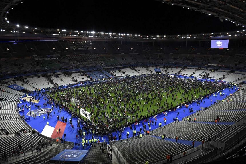 Spectators gather on the pitch of the Stade de France stadium after a series of gun attacks occurred across Paris as well as explosions outside the national stadium.