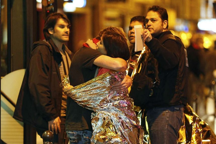 People hugging each other before being evacuated by bus, near the Bataclan concert hall in central Paris, on Nov 14, 2015.