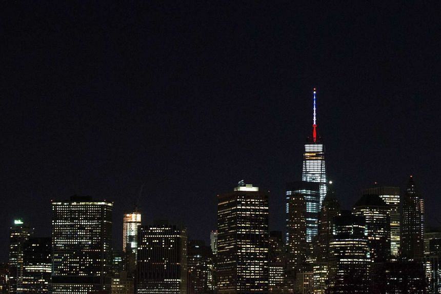 One World Trade Center's spire is shown lit in French flags colors of white, blue and red.