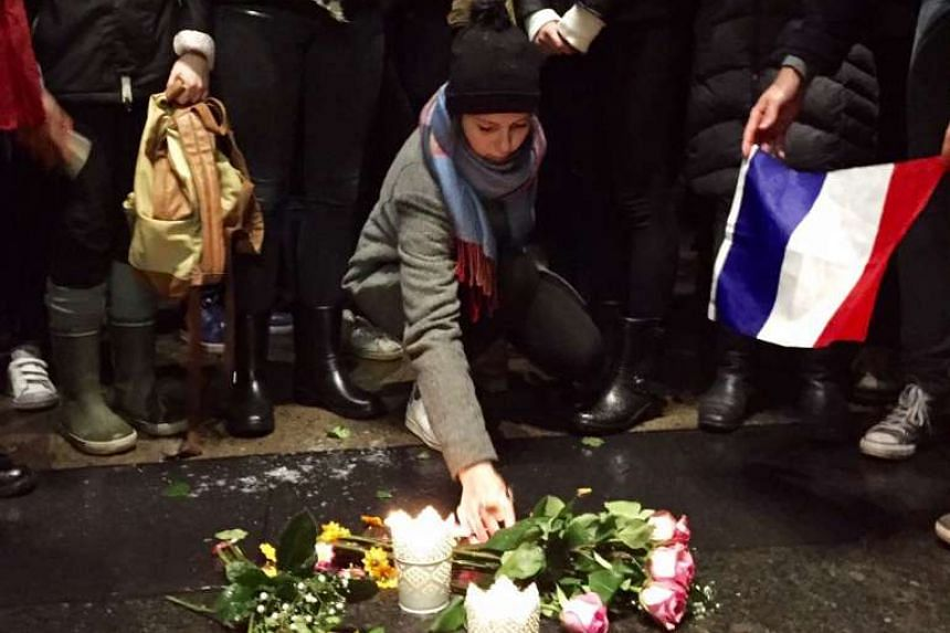 A woman lights candles as hundreds of people gather in downtown Montreal to pay tribute to the victims of the deadly attacks in Paris.
