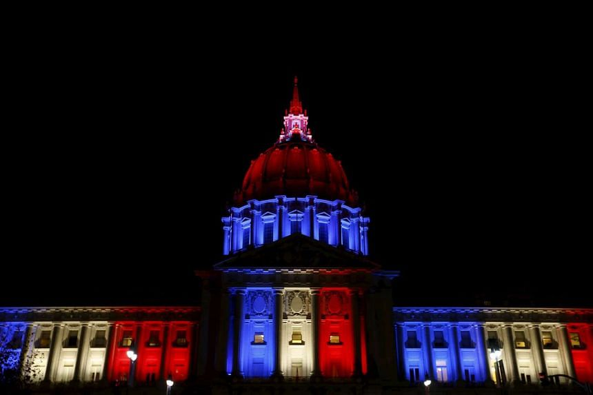 San Francisco City Hall is lit up with blue, white and red, the colors of the French flag.