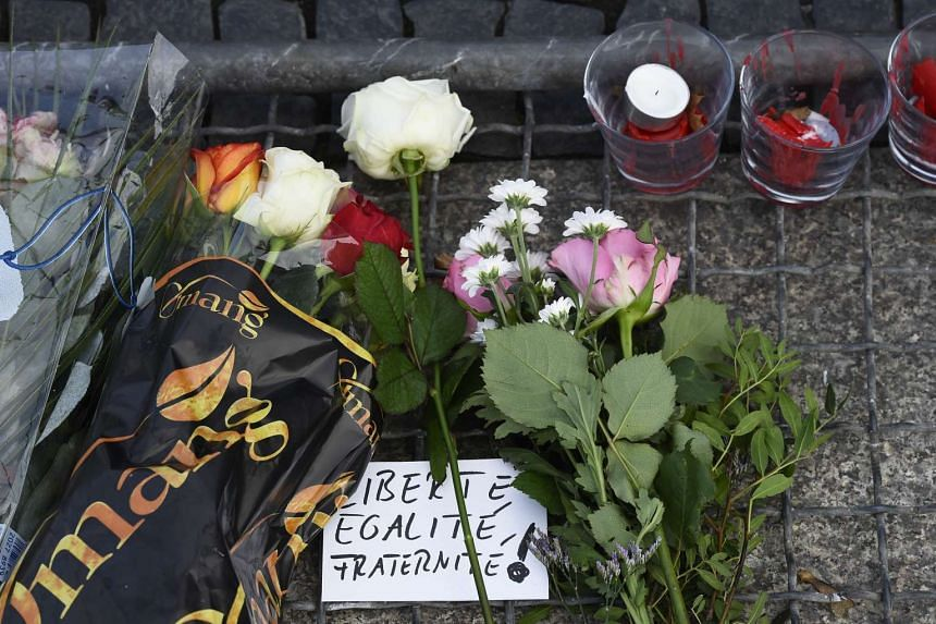 "A note reads "" Liberty, equality, fraternity"" near flowers placed outside French Embassy in Berlin."