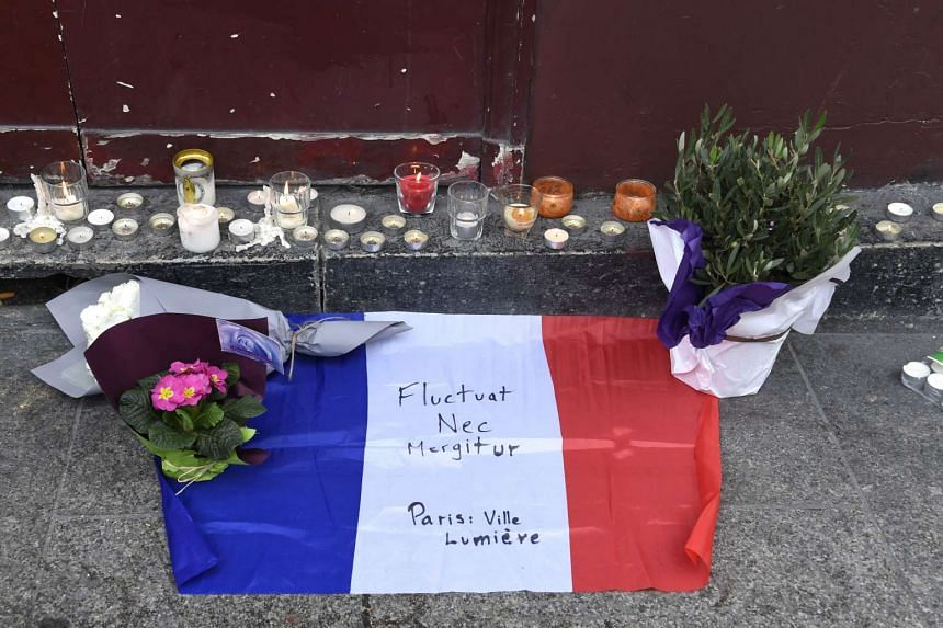 """Flowers, candels and the French national flag with the Latin, """"Tossed but not sunk"""" the motto of Paris writen on it."""