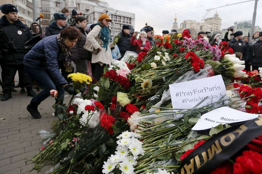 A woman puts flowers near the French Embassy in condolence to the victims of the Paris attacks, in Moscow, Russia, on Nov 14, 2015.