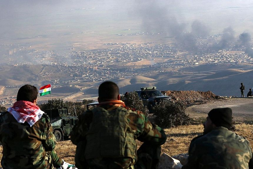 Iraqi Kurdish fighters looking on as smoke billows during an operation by their forces that was backed by US-led strikes in the northern Iraqi town of Sinjar on Thursday to retake the town from the ISIS extremist group and cut a key supply line to Sy