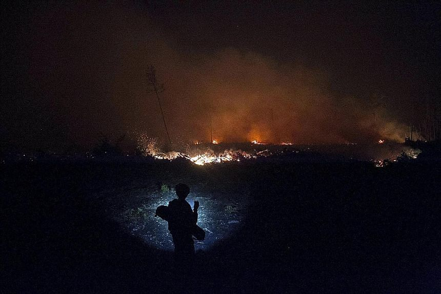 A resident with a flashlight watching as a fire burned on peatland in Central Kalimantan this month. During local elections season, there is a higher possibility of land parcels, handed out as campaign incentives by errant regional leaders, being cle