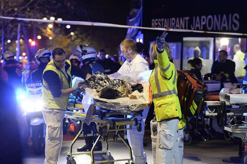 Rescuers evacuating an injured person near the Bataclan concert hall in central Paris, early on Nov 14, 2015.