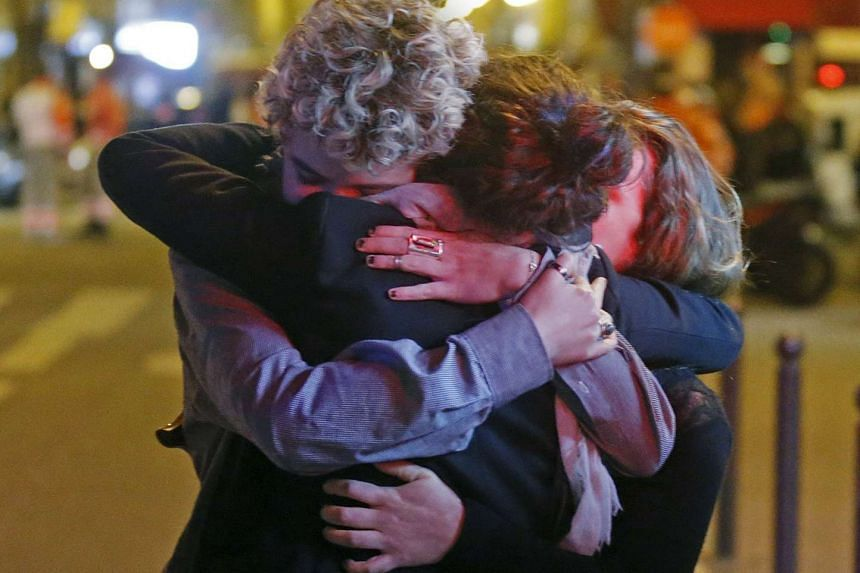 People hugging on the street near the Bataclan concert hall following fatal attacks in Paris, France, on Nov 14, 2015.