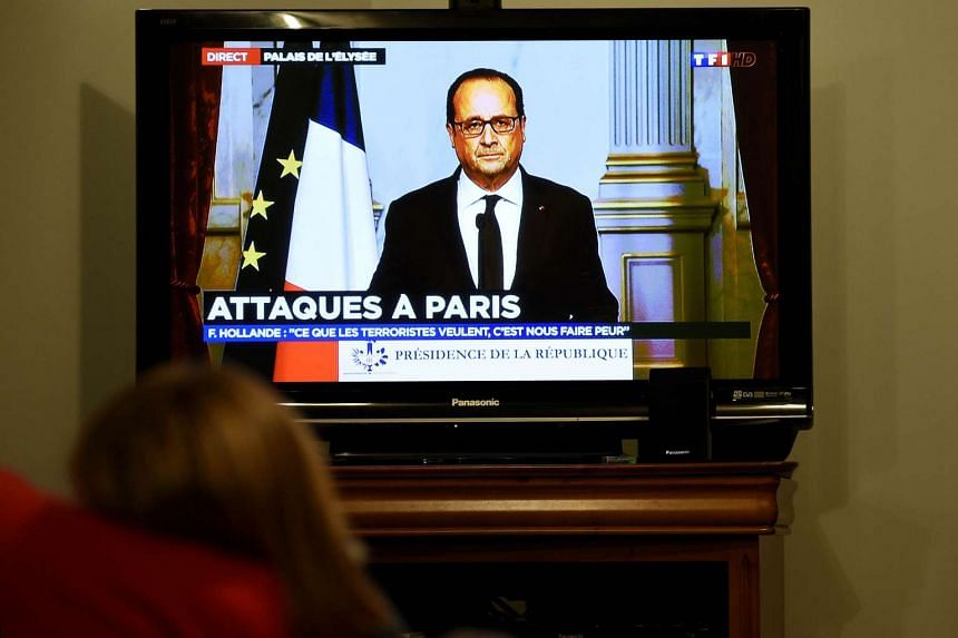 A person watching TV as French President Francois Hollande addresses the nation.