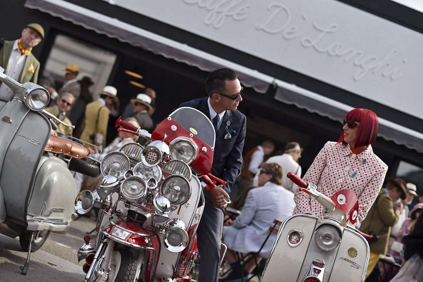 Many visitors at the Goodwood Revival are dressed in period costumes to match the vintage cars on display.