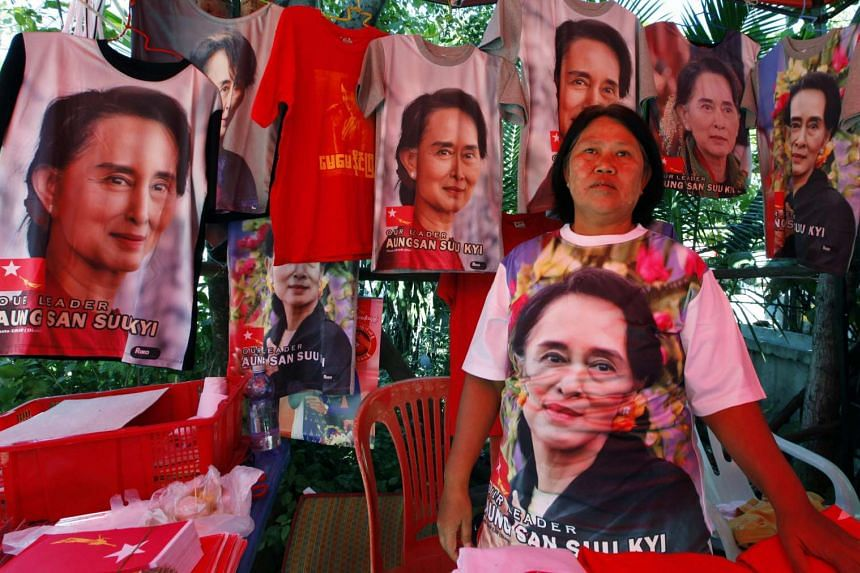 A member of the National League for Democracy party selling T-shirts with portraits of Myanmar leader Aung San Suu Kyi in Mandalay yesterday. The NLD's parliamentary majority makes it almost certain that its nominee for president will get the post. M