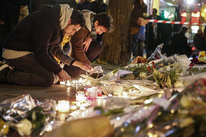 People place flowers and light candles in tribute for the victims of the 13 November Paris attacks near the Bataclan concert venue in Paris, France, Nov 14, 2015.