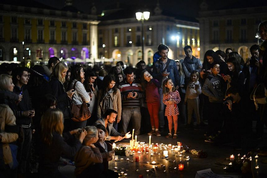 People light candles on Comercio square in Lisbon during a solidarity gathering for victims and families following a series of terror attacks in the French city of Paris.