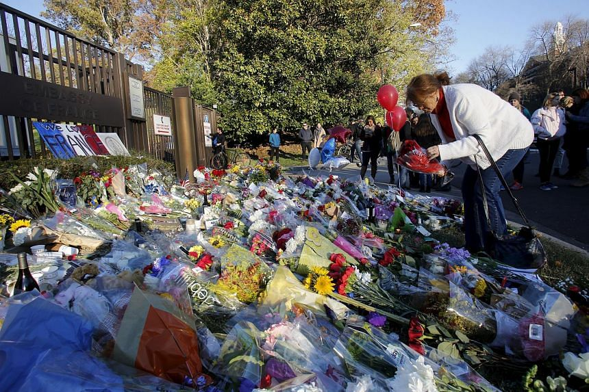 A woman places flowers for the victims of the Paris attacks in front of the French embassy in Washington.