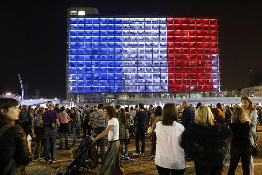 The Tel Aviv Municipality building is illuminated with the colours of the French national flag as people gather to show solidarity for the victims of the attacks in Paris.