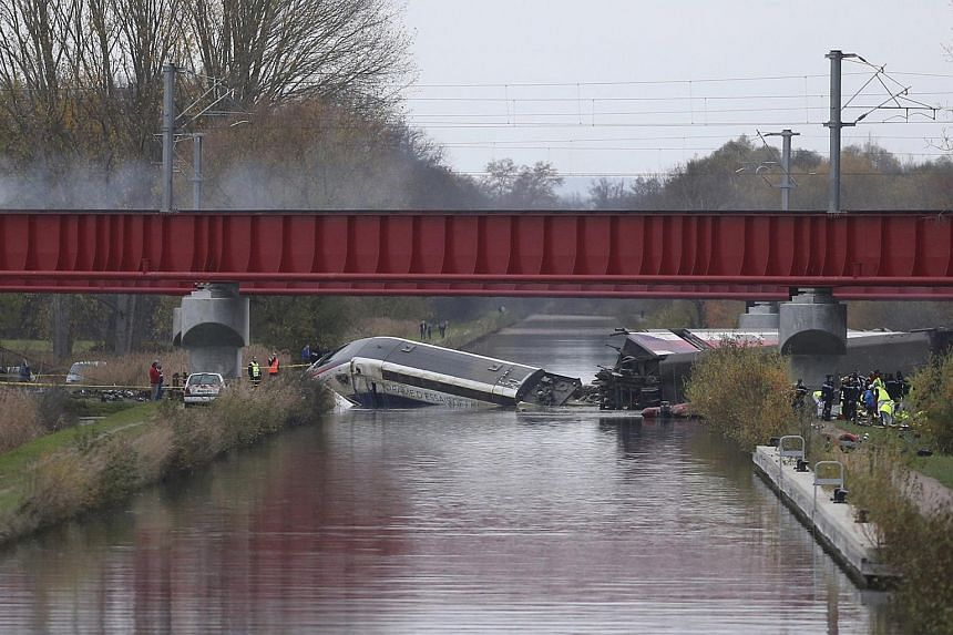 Rescue workers work around the wreckage of a test TGV train that derailed and crashed in a canal outside Eckwersheim, France, on Nov 14, 2015.