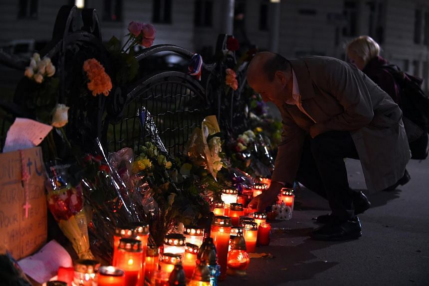 People light candles and place flowers to pay tribute for the victims of the Paris attacks, in front of the French Embassy in Vienna.
