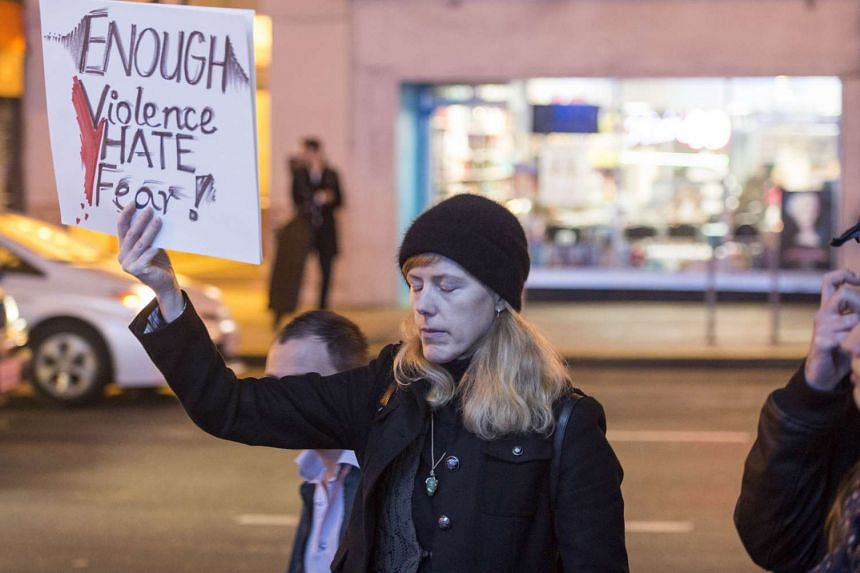 A woman holds up a sign during a vigil in front of the French Consulate General in San Francisco, California.