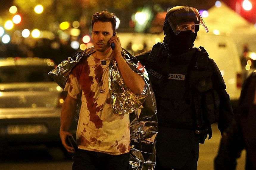 A French policeman assisting a blood-covered victim near the Bataclan concert hall following the attacks in Paris on Friday. France remains under a nationwide state of emergency.