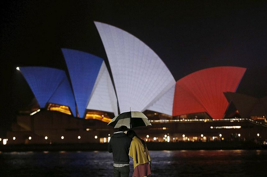 The blue, white and red colours of France's national flag were projected onto the Sydney Opera House yesterday, in a show of Australian solidarity with the French. It was one of several global landmarks similarly lit up. Rescuers evacuating people fo