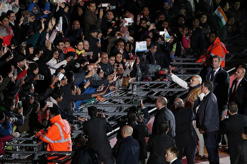 Mr Narendra Modi waving to the crowd as he walked around London's Wembley stadium after addressing a welcome rally in his honour last Friday.