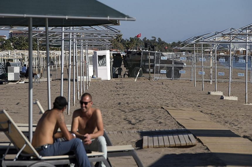 People sitting at the beach in front of barriers to the Group of 20 summit zone in Antalya, Turkey, yesterday. Tourists are not allowed to stay in hotels in Antalya's Belek area over the summit period, and air and sea security systems are in place in
