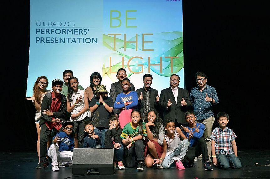 (Back row, from right) Guitarist Regi Leo, music director Jeremy Monteiro, The Business Times editor Alvin Tay, creative director Jeremiah Choy and Straits Times Schools programme editor Serene Goh posing with ChildAid performers at the Mastercard Th