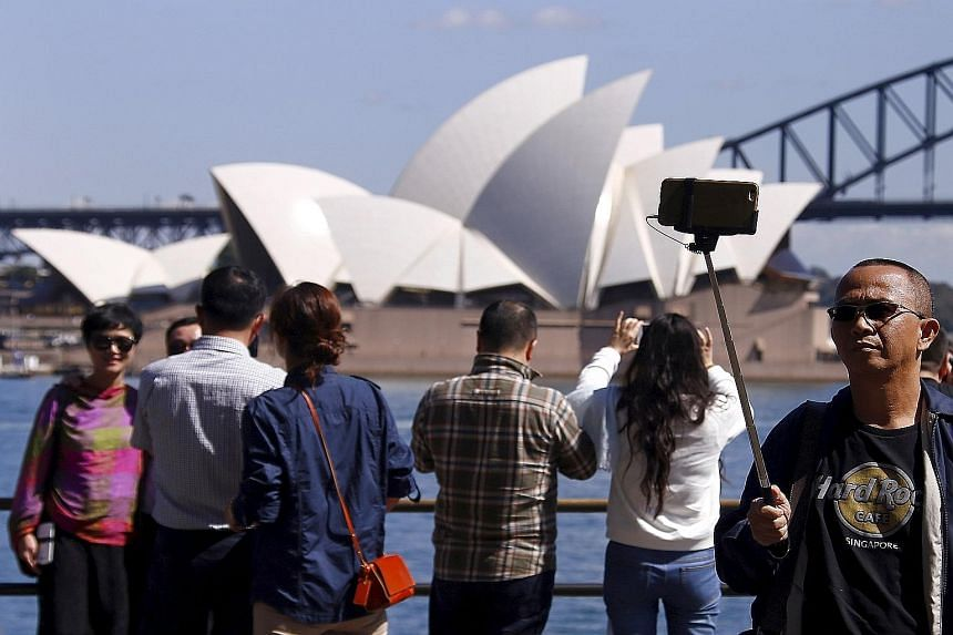 Chinese tourists taking pictures in front of the Sydney Opera House. The number of Chinese tourists overtook those from New Zealand in September.