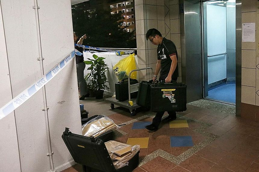 Police at the Bedok North block of flats where the murder occurred last Friday.