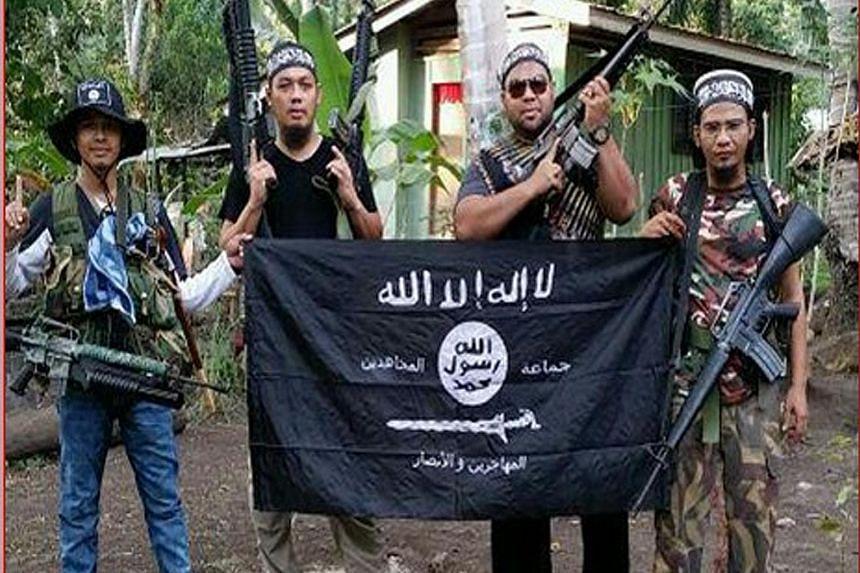 (From left) An Abu Sayyaf fighter with Malaysian militants Mahmud Ahmad, Muhammad Joraimee Awang Raimee and Muamar Gadafi, posing with an ISIS flag.