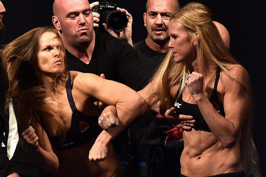 MMA fighters Ronda Rousey (left) and Holly Holm scuffle during a face-off after the weigh-in for their UFC bantamweight title fight at Etihad Stadium in Melbourne, Australia, on Nov 14, 2015.