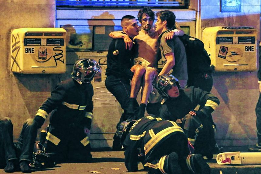 French fire brigade members aid an injured individual near the Bataclan concert hall.