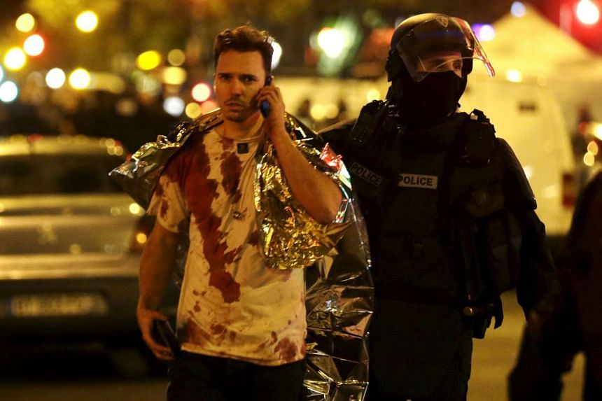 A French policeman assists a blood-covered victim near the Bataclan concert hall.