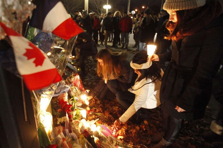 Women leave candles at the French embassy during a vigil in Ottawa on Nov 14, 2015, one day after the terrorist attacks in Paris.