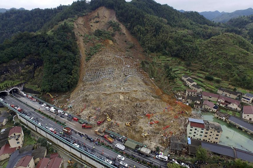 An aerial view shows rescuers searching for survivors among debris at the site of a landslide in Zhejian provine, China.