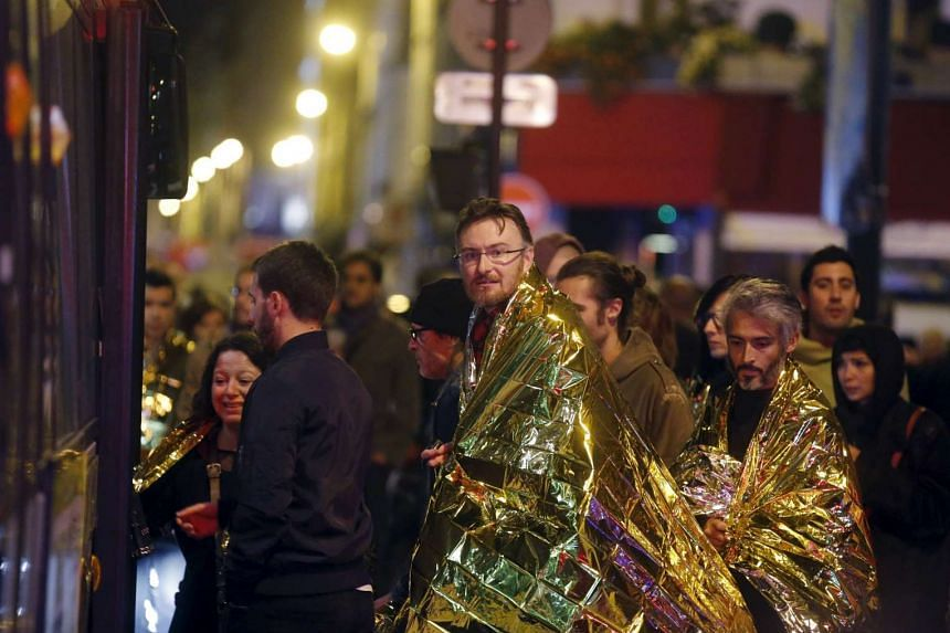 People warm up under protective thermal blankets as they are evacuated from the Bataclan concert hall.