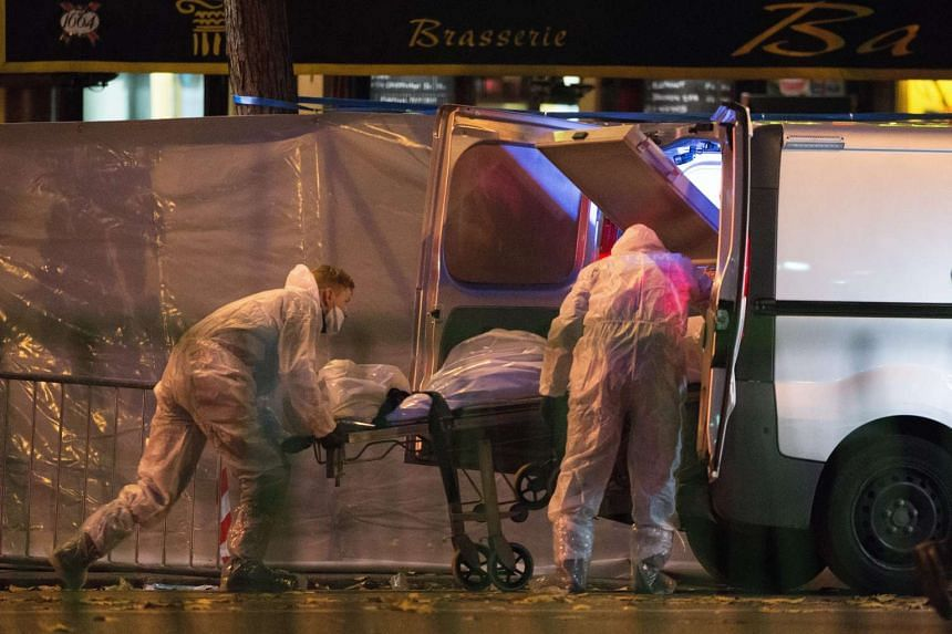 Medical staff carry the body of a victim in front of the Bataclan theatre in Paris.